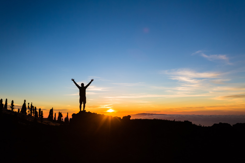 Man hiker silhouette with arms outstretched in mountains. Male runner or climber looking at sunset view. Business concept and hands up and enjoy inspirational landscape, rocky trail footpath on Tenerife, Canary Islands