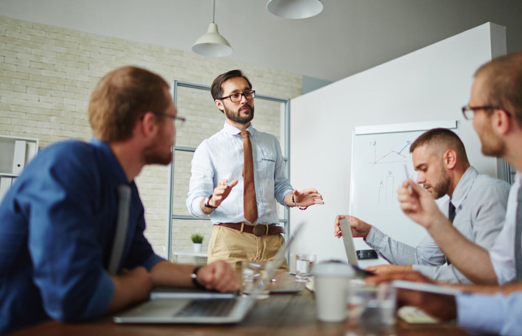 Serious businessman looking at colleagues during explanation