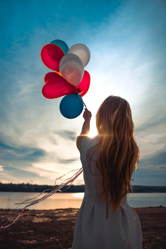 girl holding balls on the background of sunset