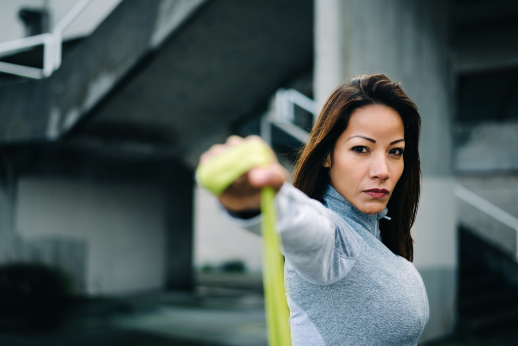 Motivated latin woman doing shoulder raises exercise with fitness resistance band. Urban outdoor strength workout.