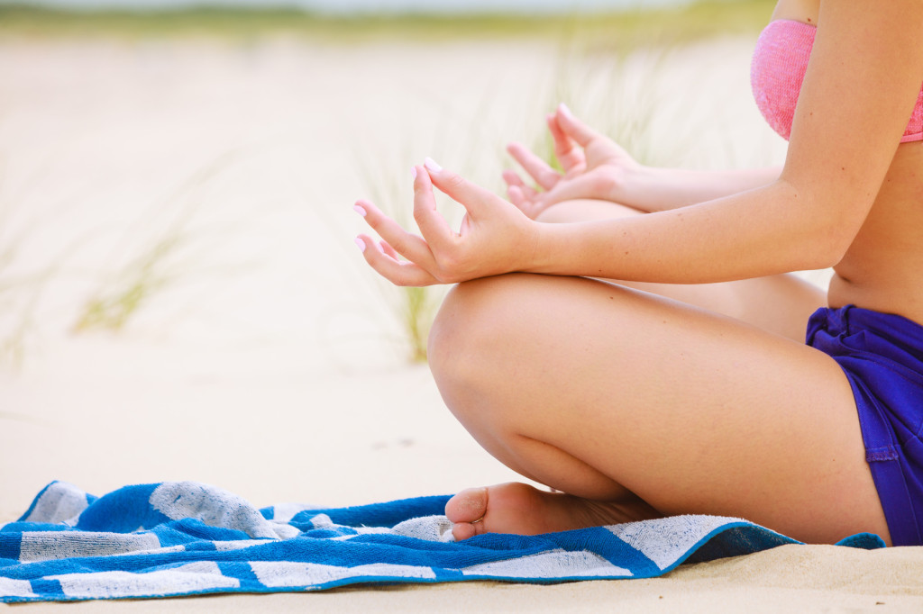 Relaxation time. Young girl spending free time on yoga exercises to relax body and mind. Woman resting on beach in summer.