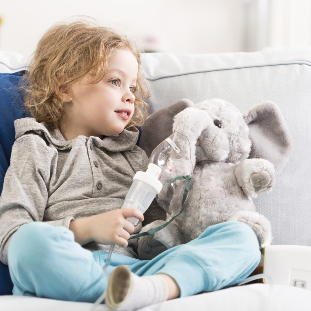 Little child sitting on a sofa with an elephant toy with oxygen mask