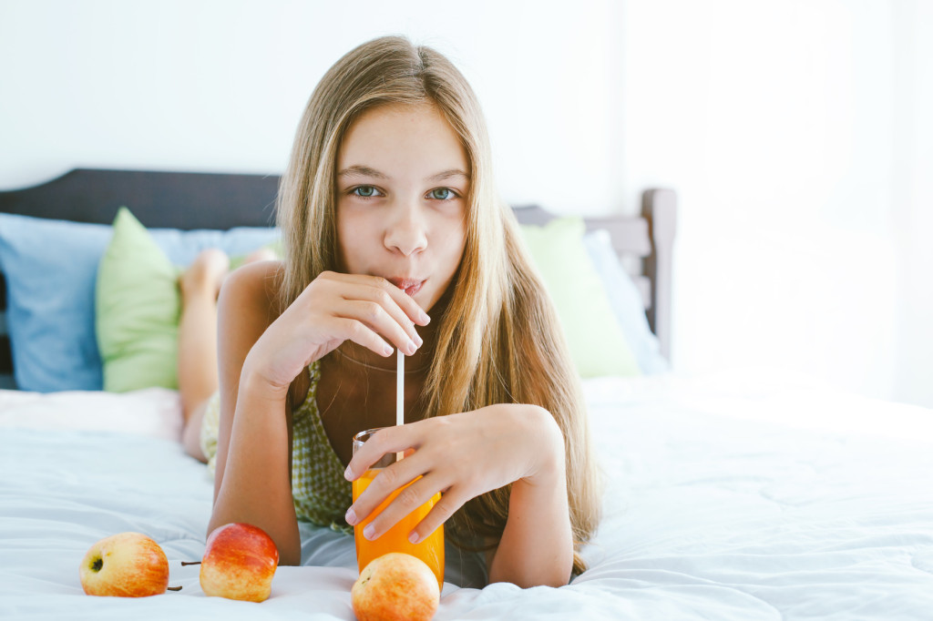 10 years old pre teen girl drinking orange juice while relaxing in bedroom. Healthy food for breakfast.