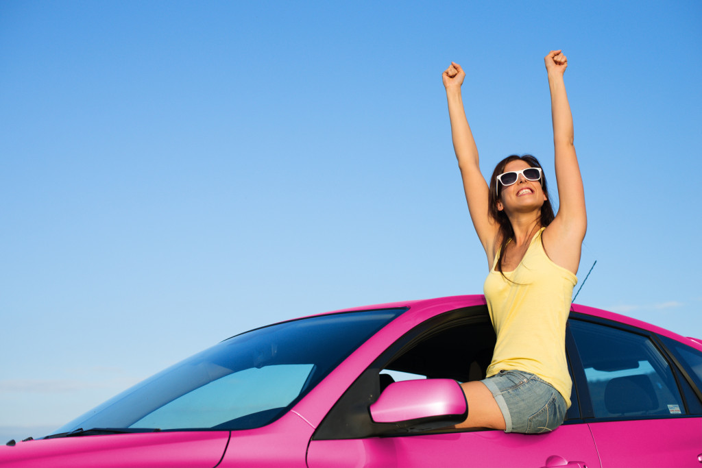 Joyful woman having fun with her new pink car raising arms up to the sky on summer road trip vacation. Freedom and driving license success concept.