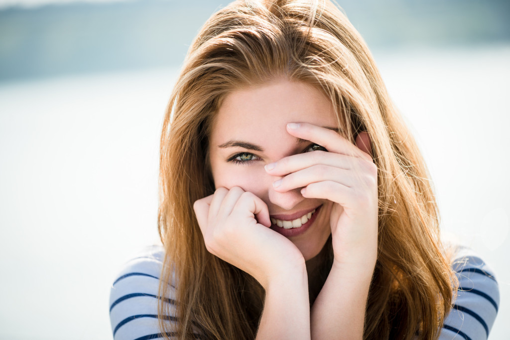 Teenager portrait - smiling girl outdoor with hands before face