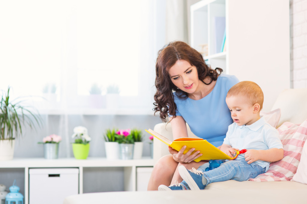 Mother with child read a book in the home room