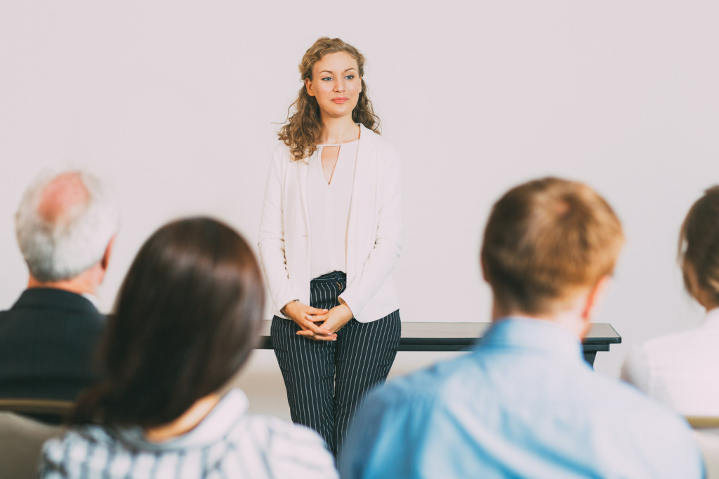 Portrait of young female business coach standing in front of audience at conference and listening question addressed to her
