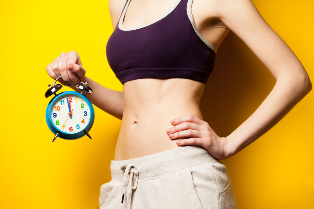 photo of perfect slim female body with alarm clock in the hand on the wonderful yellow background