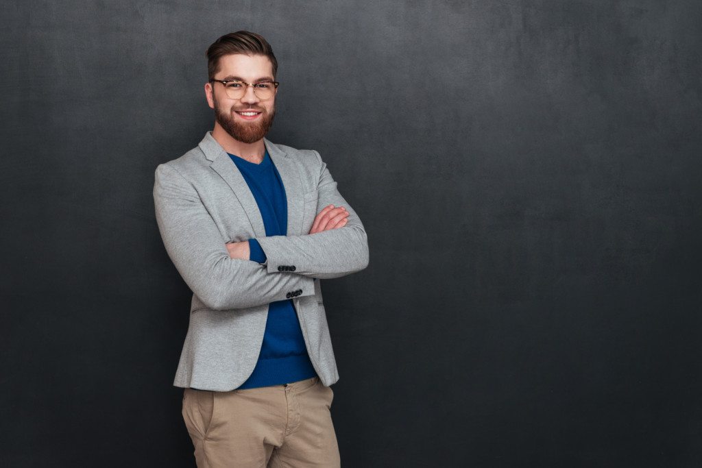 Happy handsome young businessman in glasses standign with arms crossed