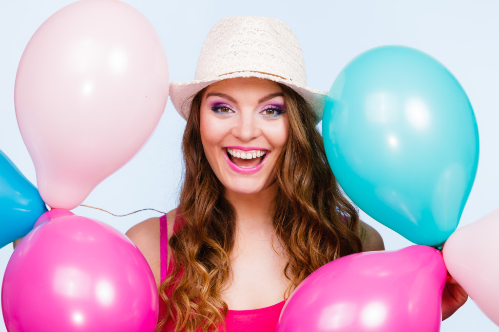 Woman charming girl playing with many colorful balloons. Summer, celebration happiness and lifestyle concept. Studio shot blue background