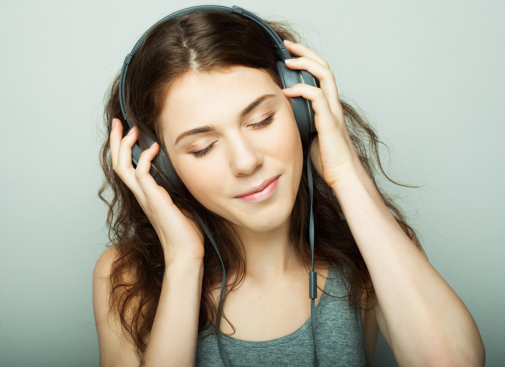 lifestyle and people concept: young happy woman with headphones listening music.