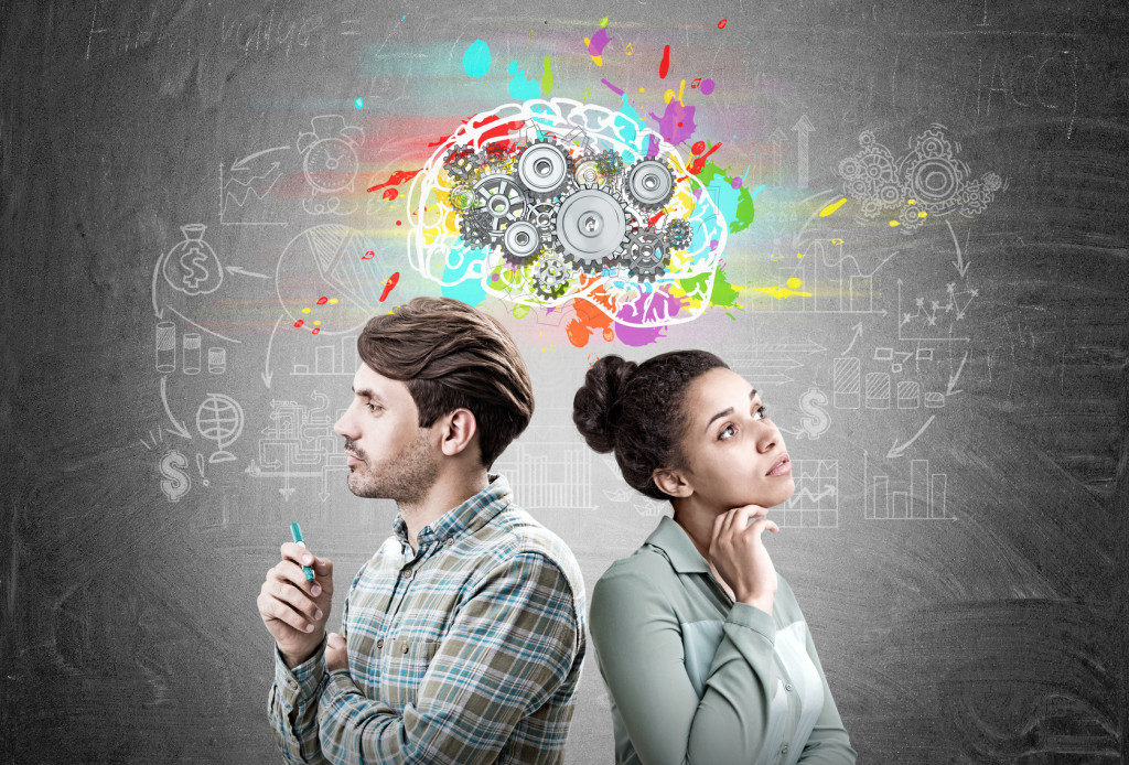 Portrait of a man and an African American woman standing back to back near a blackboard with a colorful brains sketch and cogs on it.