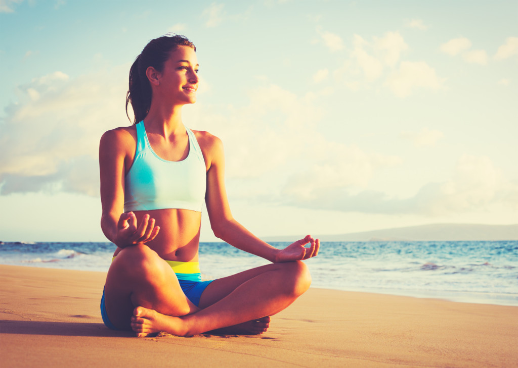 Happy young woman practicing yoga on the beach at sunset. Healthy active lifestyle concept.